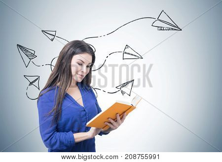 Portrait of a young smiling businesswoman wearing a blue blouse and reading an orange book. Gray background with a paper planes sketch