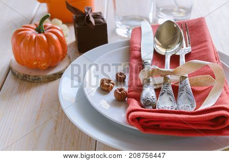 Beautiful autumn table settings and thanksgiving dinner decoration: white plate with small pumpkins and orange linen napkin with vintage cutlery. Thanksgivings Day festive background.