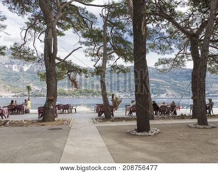 Budva - September 24 2017: People rest at tables in an outdoor cafe on the island of St. Nicholas near the town of Budva Montenegro