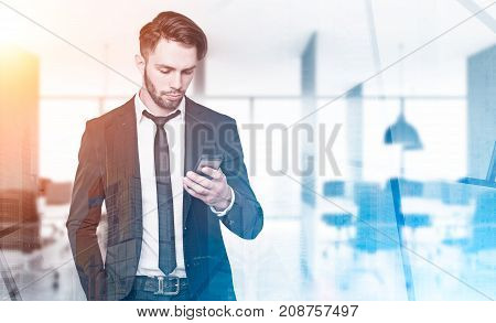 Young businessman in a suit is looking at his smartphone while standing in an office. A cityscape in the background. Mock up toned image double exposure