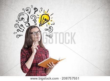 Portrait of a beautiful and pensive young woman wearing a red checkered dress and glasses and holding an open orange book. Concrete wall with question marks and a light bulb. Mock up