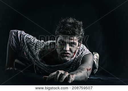 Male zombie standing on dark background, reaching hand towards camera