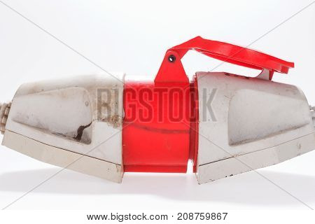 Red and white three-phase plug and socket isolated on white