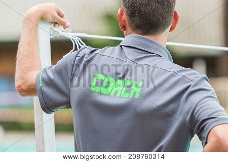 back of a coach's grey shirt with the green word Coach written on it good background for sport or coaching theme