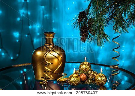 A bottle of brandy and three candles in New year and Christmas with Christmas tree branches on blurred blue background