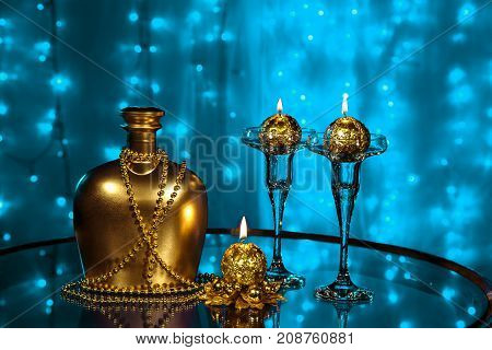 A bottle of brandy and three candles in New year and Christmas on blurred blue background
