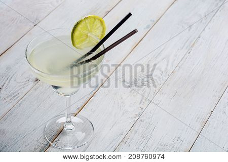 Classic lime margarita cocktail with sliced limes on wooden background .