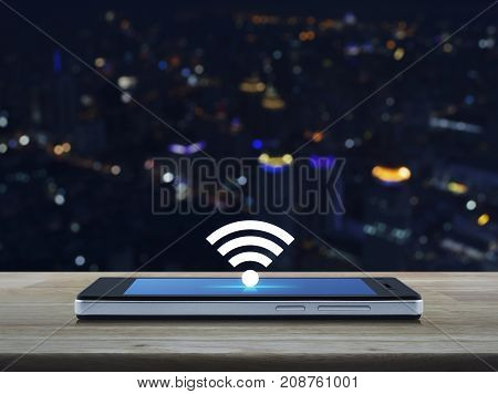 wi-fi button flat icon on modern smart phone screen on wooden table over blur colorful night light city tower Technology and internet concept