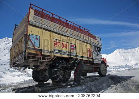 KHARDUNG LA PASS, INDIA - APRIL 21, 2016: Driver is fixing tyre-protection chains at Kardung La pass - one of the highest motorable road (5360 m) in the world.