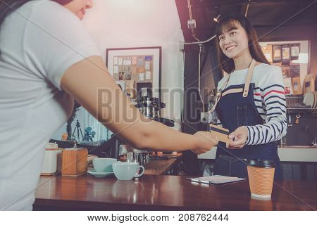 Young beautiful Asian woman barista wear blue apron and customer payment by credit card at bar counter in coffee shop with smile face.Concept of cafe and coffee shop small
