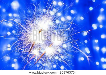 Three Bengal fire sparkles in New year and Christmas on blurred blue background