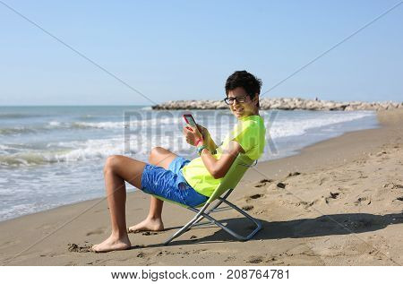 smiling caucasian boy reads an ebook sitting on the beach chair at the seashore in summer with a fluorescent t-shirt
