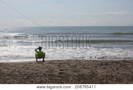 Lonely Young Boy At The Summer Sea Shore Rests