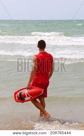 Muscular Lifeguard At Shore At The Sea Shore In The Beach Of The