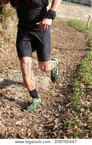 Muscular Athlete's Legs During The Country Race On The Trail