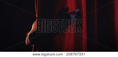 Cropped hand in black glove behind curtain at stage