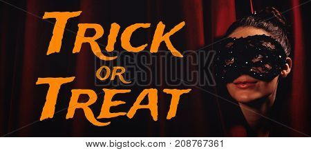 Graphic image of trick or treat text against artist in mask peeking through curtain
