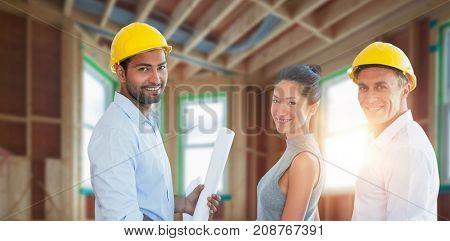 Portrait of architect holding blueprints against house under construction