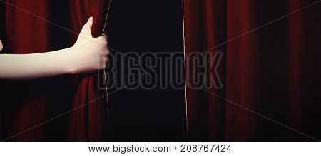 Cropped hand of performer holding curtain at stage