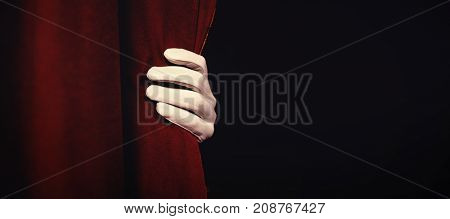 Cropped hand in glove holding maroon curtain at stage