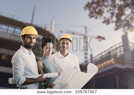Portrait of architects blueprint against cranes at construction site
