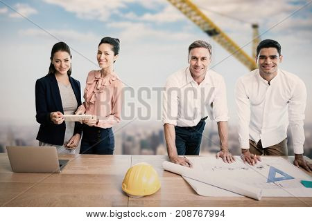 Portrait of architects at table against 3d image of yellow crane