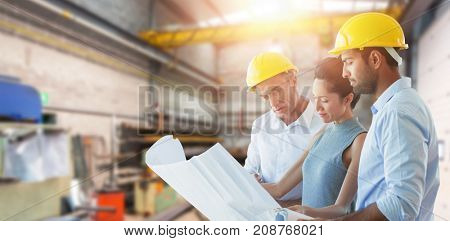 Architects discussing over blueprint against workshop