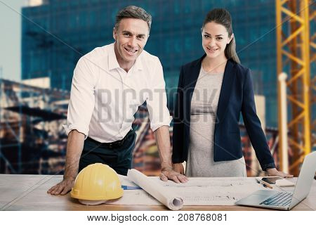 Portrait of architects standing at table against construction site