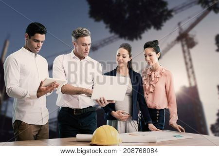 Male architect showing laptop to coworkers against cranes at construction site during day