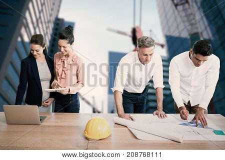 Architects working at table against composite image of studio shoot of a crane