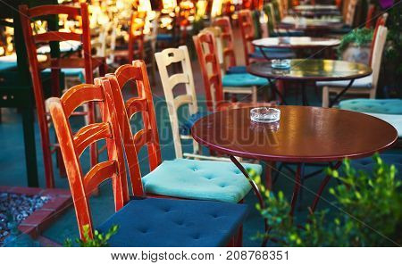 Closeup view on colorful wooden chairs of a restaurant in Greece.