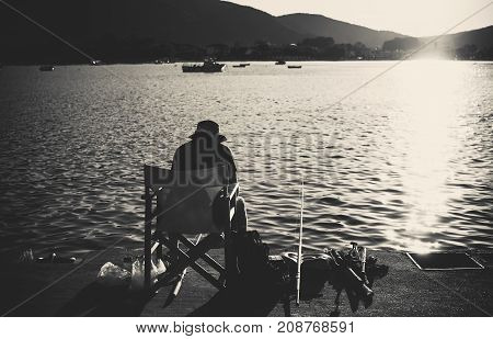 One lonely man sitting and fishing on sea dock during sunset in black and white.