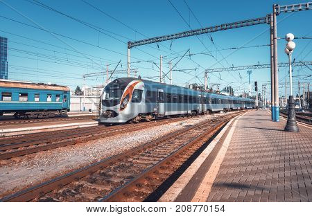 High speed train at the railway station at sunset in Europe. Modern intercity train on the railway platform. Urban scene with beautiful passenger train on railroad. Railway transportation. Vintage