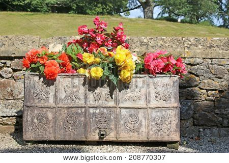 Lead flower casket full of begonia flowers