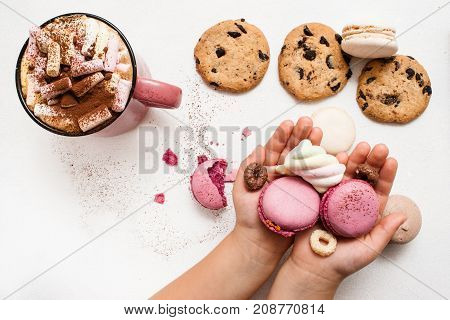 Sweet morning with hot cocoa and favorite cookies. Unrecognizable child with colorful macaroons in palms, chocolate scone and delicious drink with marshmallow on white table nearby, top view