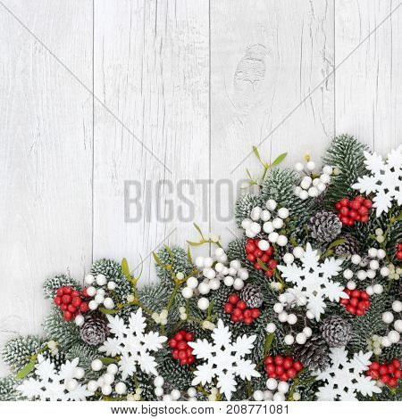 Christmas snowflake background border with holly, mistletoe, ivy, fir and pine cones on rustic  white wood.