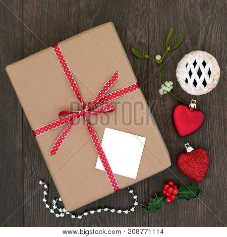 Christmas present with bow, gift tag, holly, mistletoe, mince pie and heart shaped bauble decorations with bead string on oak background. Top view of holiday giving concept.