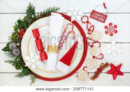 Christmas dinner table place setting with dinner plate, napkin, santa hat, candy canes and cracker, mince pies, spice, decorations, holly, cedar, ivy and mistletoe on rustic white wood background.