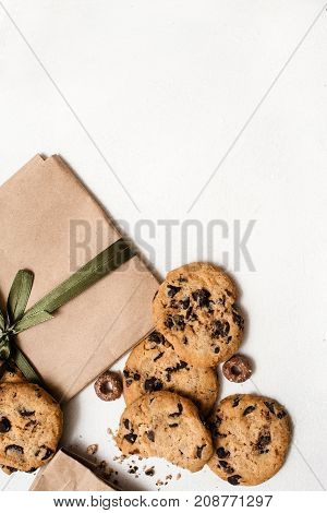 Fond of sweets and gifts for holidays. Small elegant present on white table with homemade chocolate scones nearby, top view picture with free space