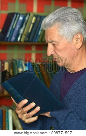 mature man reading book at home library