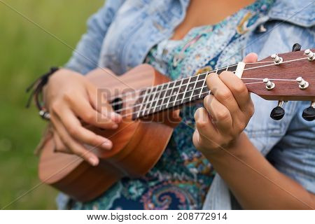 Closeup photo of young woman playing on Ukulel.