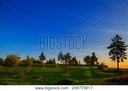 rural house and field of green grass against the backdrop of a colorful evening sky at sunset beauty of nature Belarus