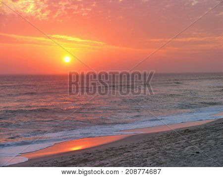 SUN SETTING UNDER A GOLDEN RED SKY OVER THE HORIZON OF THE ATLANTIC OCEAN AND REFLECTING IN THE WATER