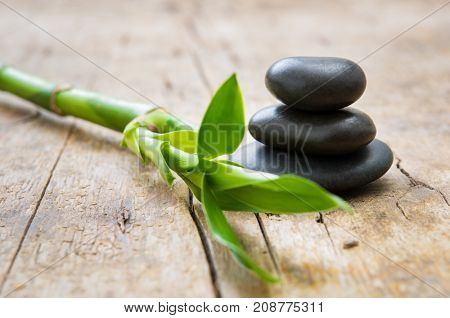 Close up of stacked hot stones with green bamboo on wooden table. Black massage stones necessary for a hot rock treatment in a spa setting. Beauty and spa treatment concept.