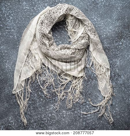 black and white cotton scarf with fringe on a dark grey textured cement background top view