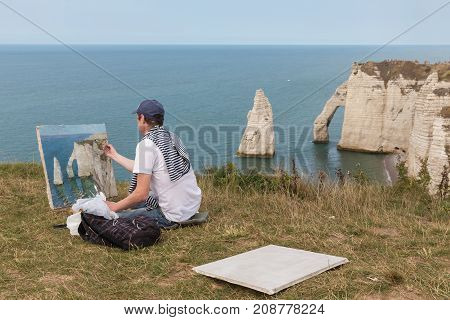 ETRETAT, FRANCE - AUGUST 25, 2017: Artist is making a painting of the famous Elephant cliffs near Etretat in Normandy, France