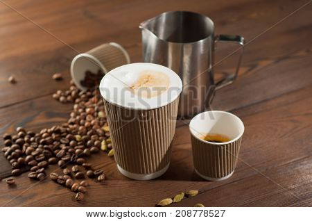 Latte and espresso in paper cups on a wooden background with scattered coffee beans