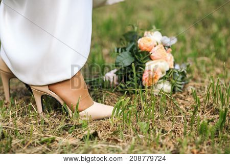 Bride's Cream White Shoes And Beautiful Bouquet On The Green Grass. Wedding Day.