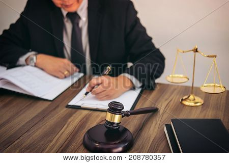Gavel on wooden table and Lawyer or Judge working with agreement in Courtroom theme Justice and Law concept.