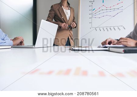 Business people are working in office presentation in front of Whiteboard business woman leader presentation to her colleagues and business strategy and pointing to the board.